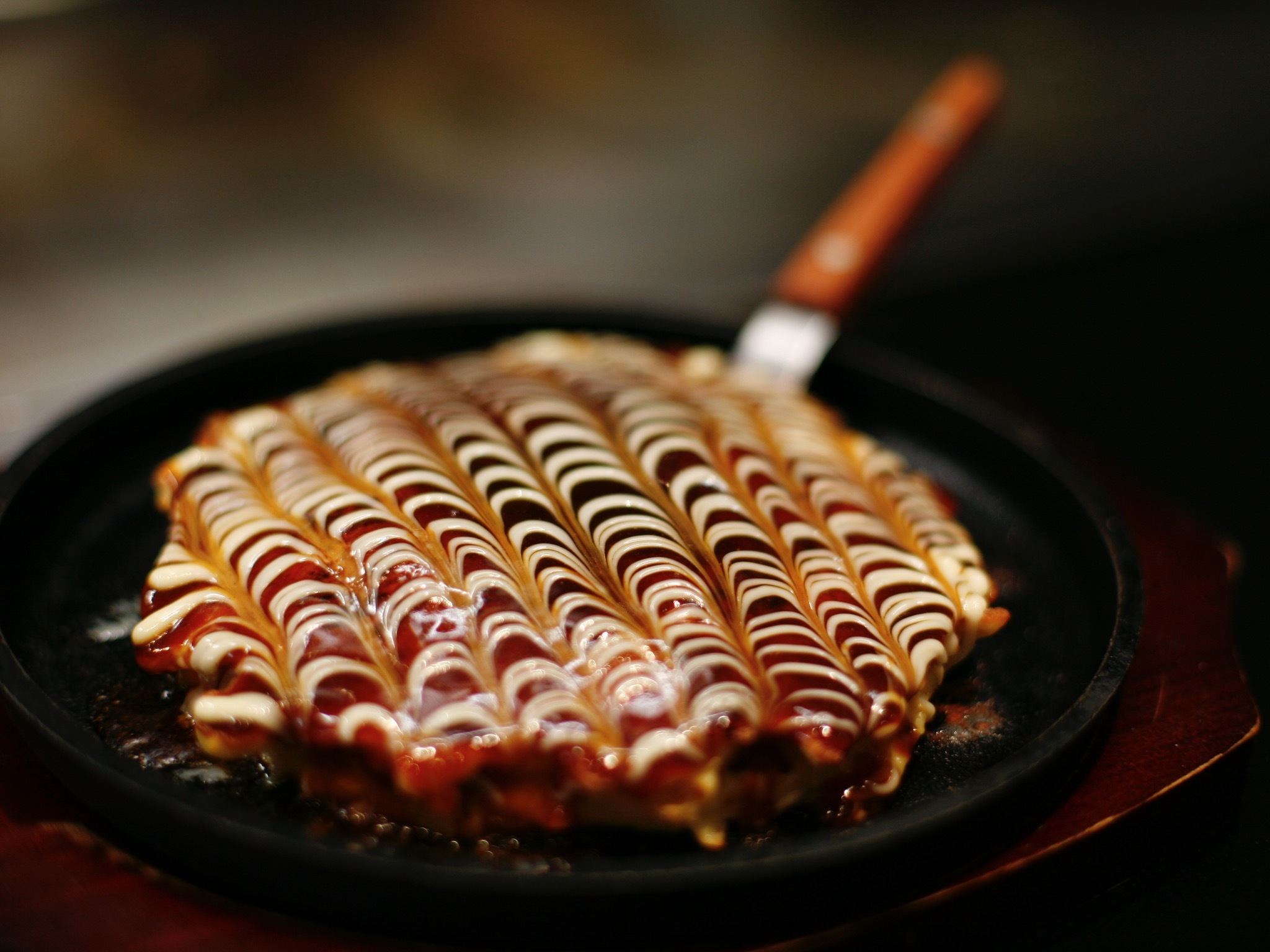 A close up shot of an okonomiyaki in an iron pan at Ju Ge Mu Shi