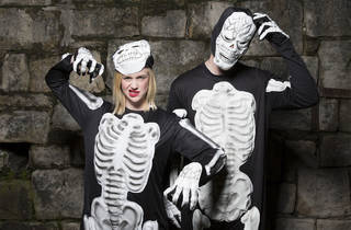 Two people standing up against a brick wall wearing skeleton hal