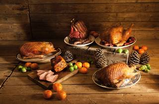 A generic shot of various Christmas roast meats on plates and wo