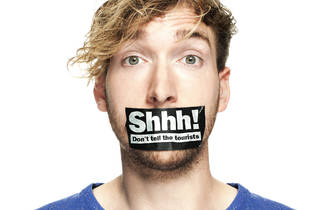 A man against a white background with duct tape over his mouth w
