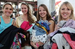 A shot of four women holding piles of clothes at The Clothing Ex