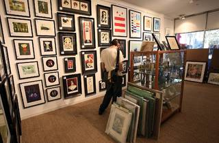 An interior shot at Outre Gallery showing a man browsing a wall