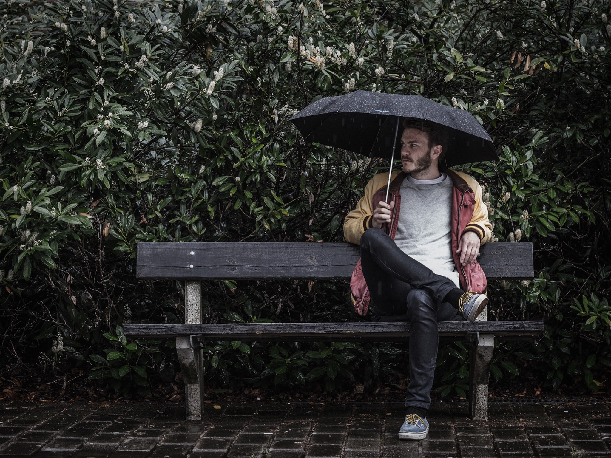 A generic image of a man sitting at a bench with an umbrella whi