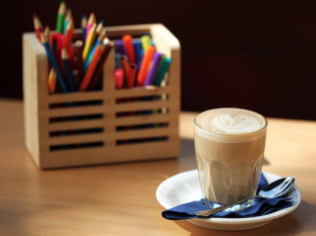 A shot of a latte coffe with a box of coloured pencils and marke