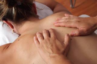A set of hands massaging a woman's back
