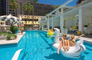Two girls lying on an inflatable swan in the pool