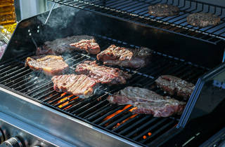 Steaks sizzle on a large barbecue