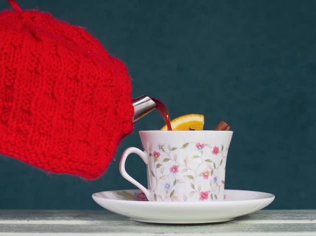 A shot of a tea pot covered in a tea cosy pouring out mulled win