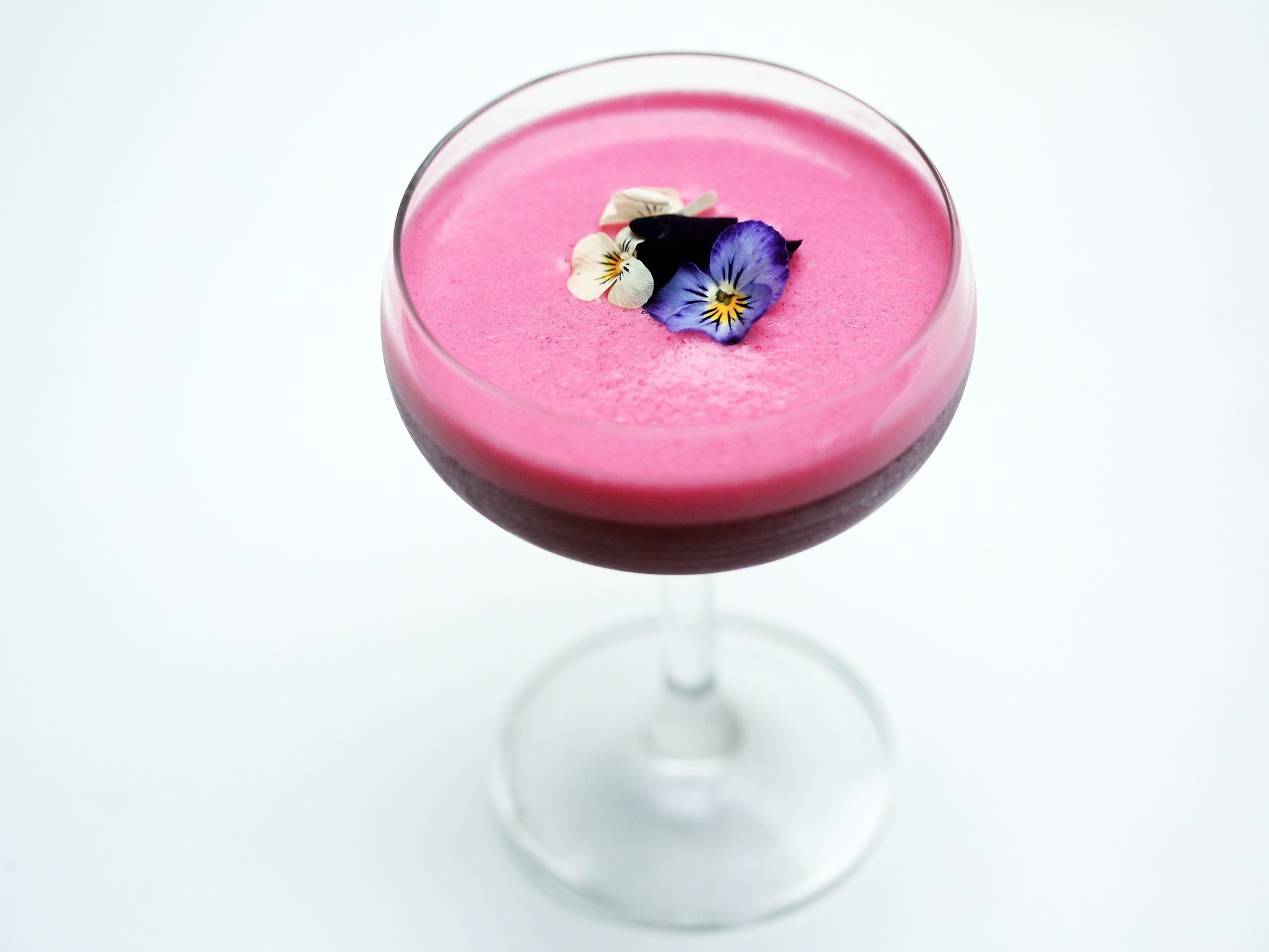 A close up shot of a purple cocktail with flowers on the top  at