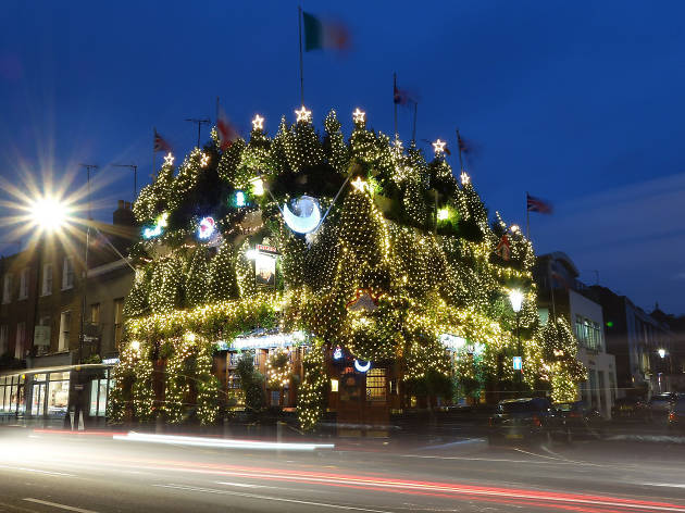 The Churchill Arms pub covered in Christmas lights.