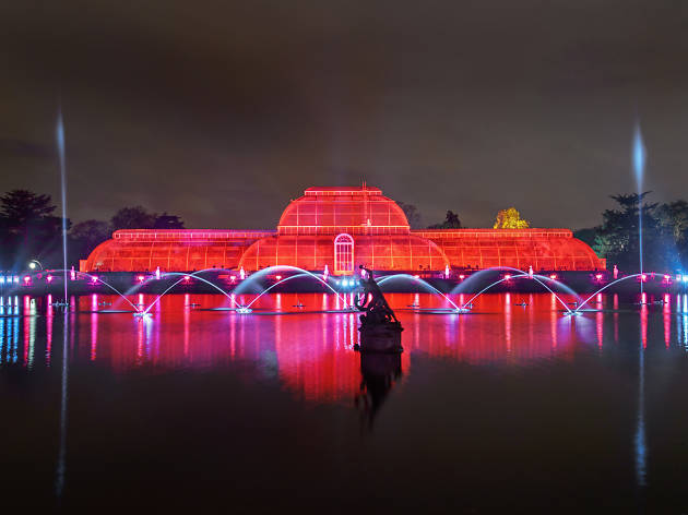 A greenhouse at Kew Gardens lit up with red light for Christmas.