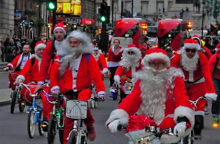 Santas on their bikes ride down Whitehall.