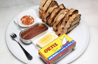 A close up shot of a tin of anchovies next to a bunch of toast,