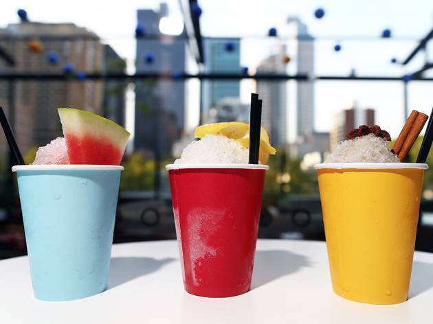 A shot of three cocktails in coloured paper cups on a table at L
