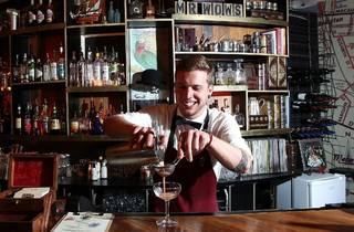 A bartender behind the bar at Mr Wow's Emporium pouring a cockta