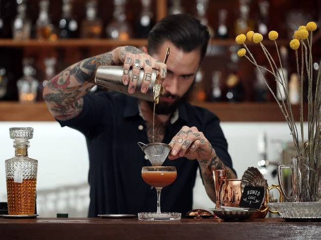 A bartender behind the bar at Romeo Lane pouring a cocktail from