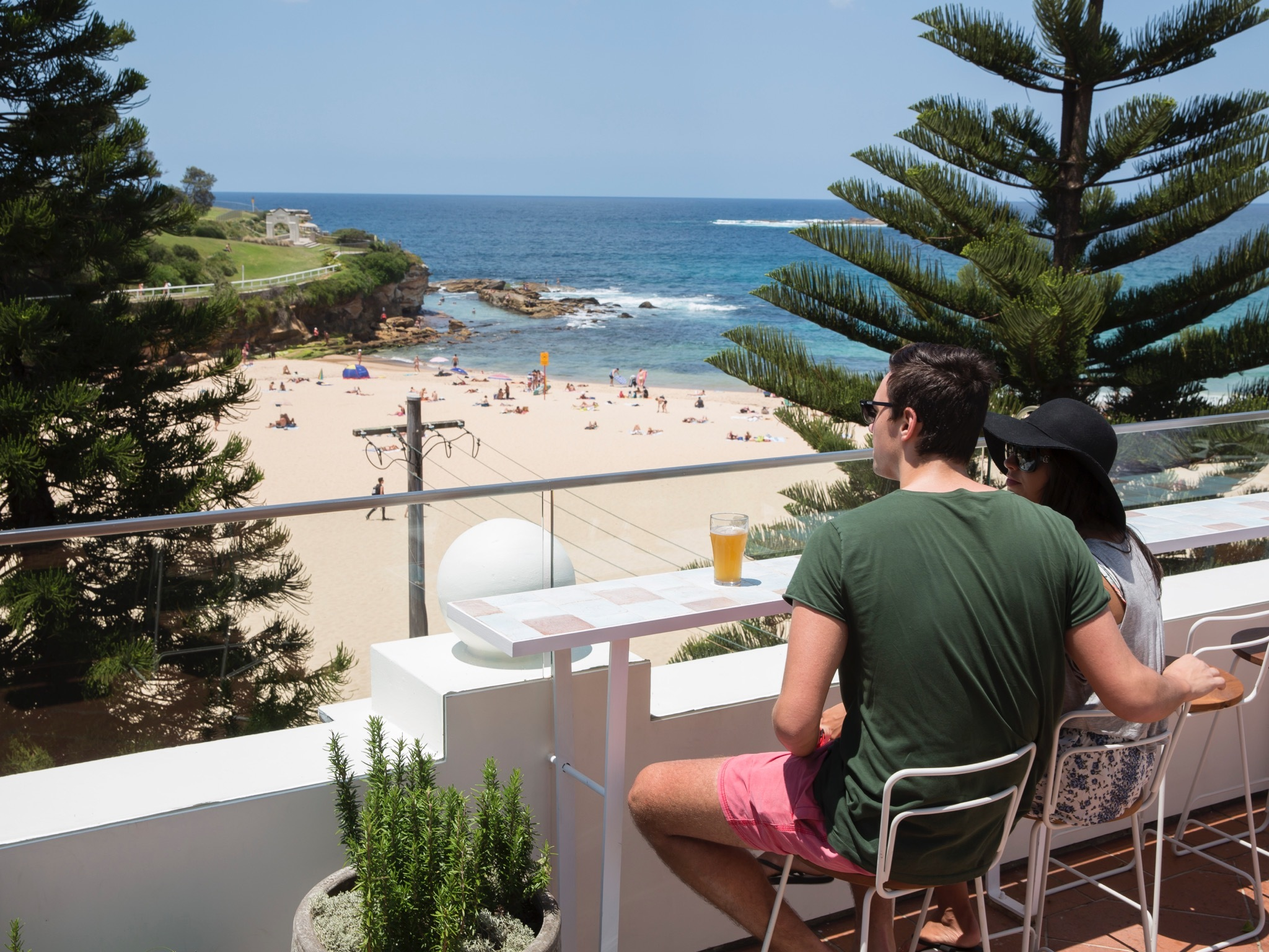 A couple enjoying a drink whilst overlooking Coogee Beach
