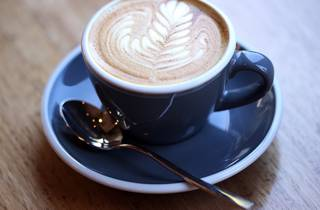 A close up shot of a cup of coffee with latte art at Hammer and