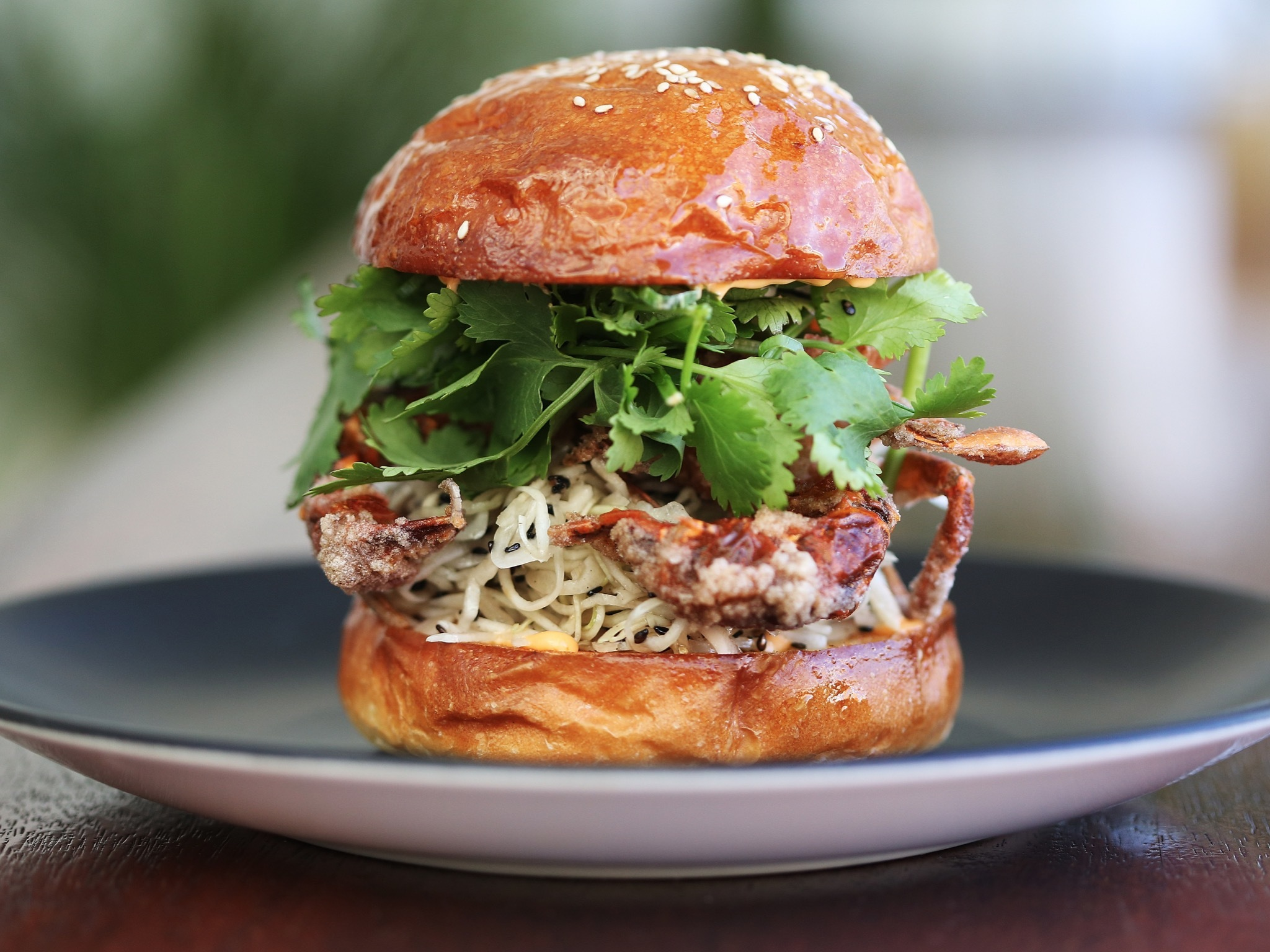 A soft shell crab burger with sriracha mayonnaise and coleslaw a