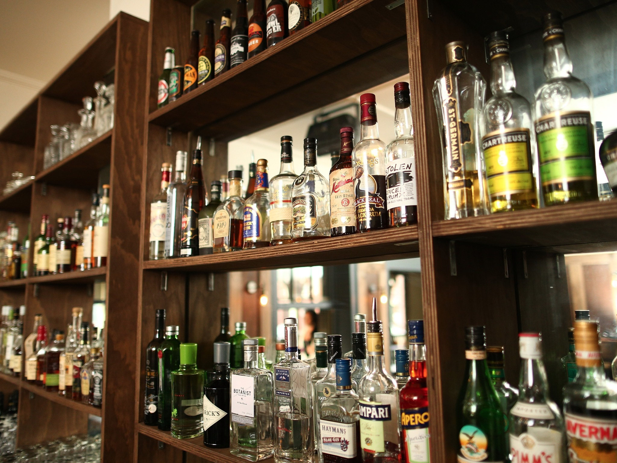 A shot of a shelving unit behind the bar full of spirit bottles