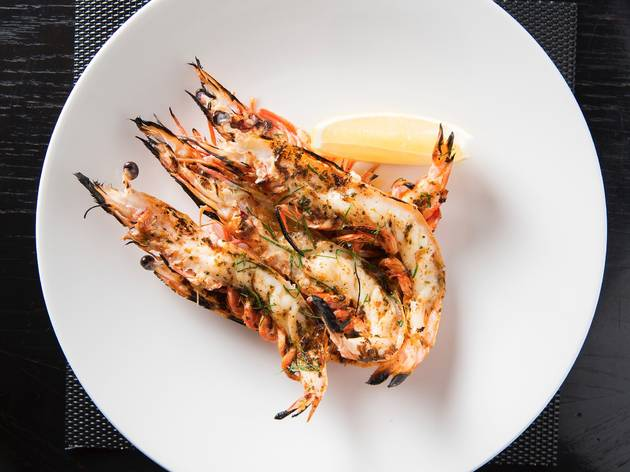 Charred prawns served with a lemon wedge