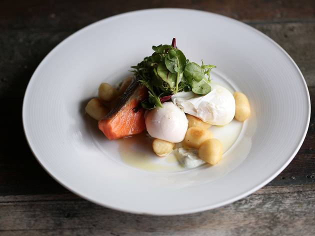 A plate of poached eggs with house-cured salmon, fried potato gn