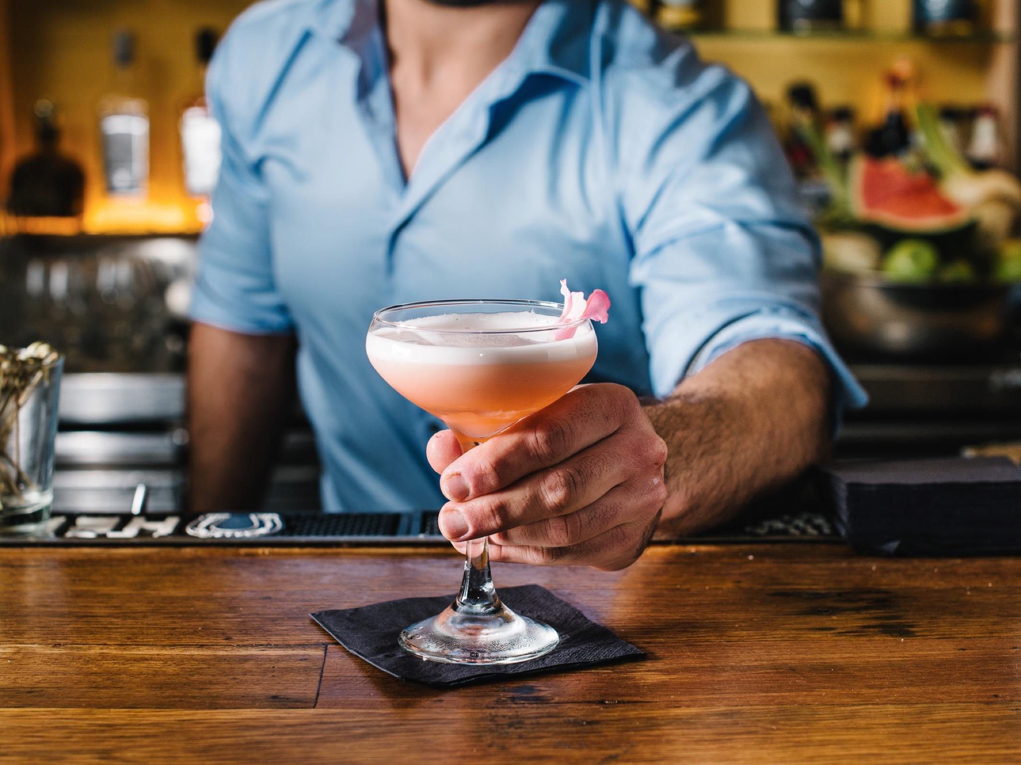 A bartender handing a cocktail over the bar