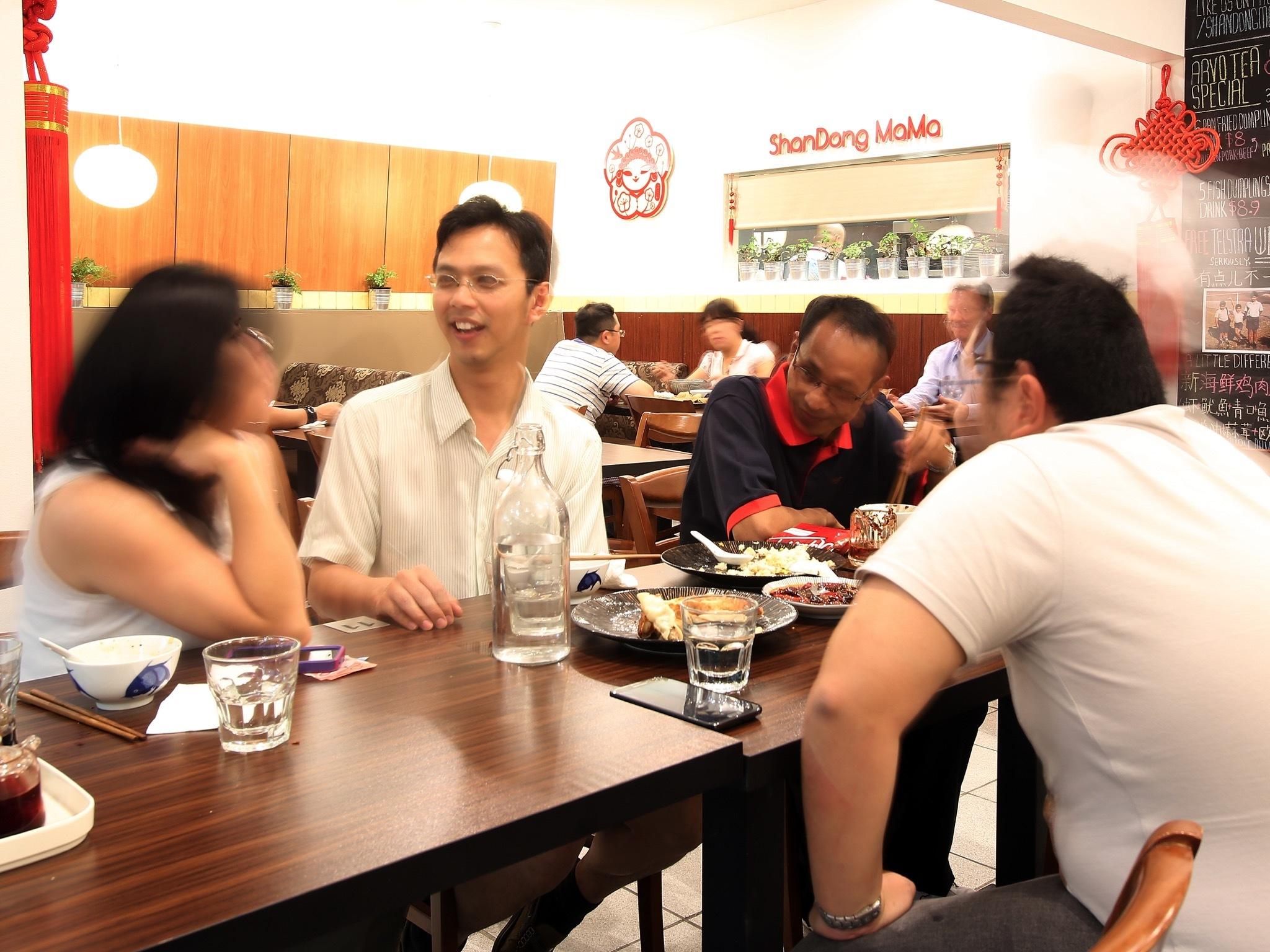An interior shot at ShanDong MaMa shwoing a group of people sitt