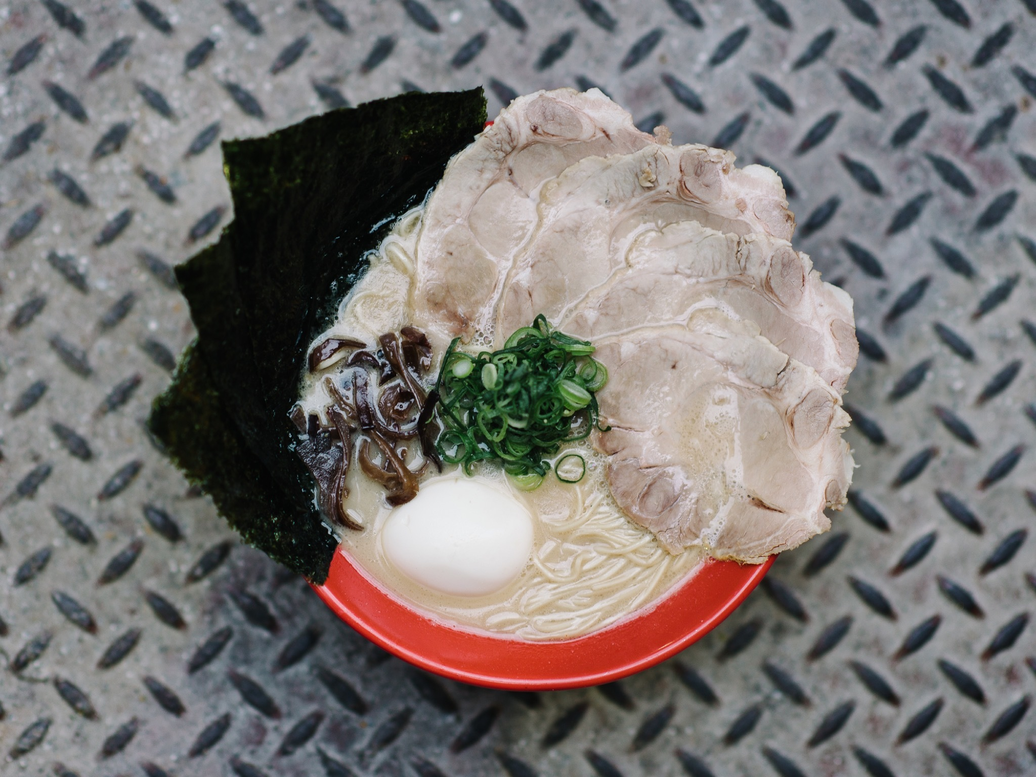 A top down shot of a bowl of ramen, with egg, noodles, nori, spr
