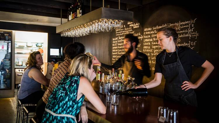 Sommeliers pour out wine for customers