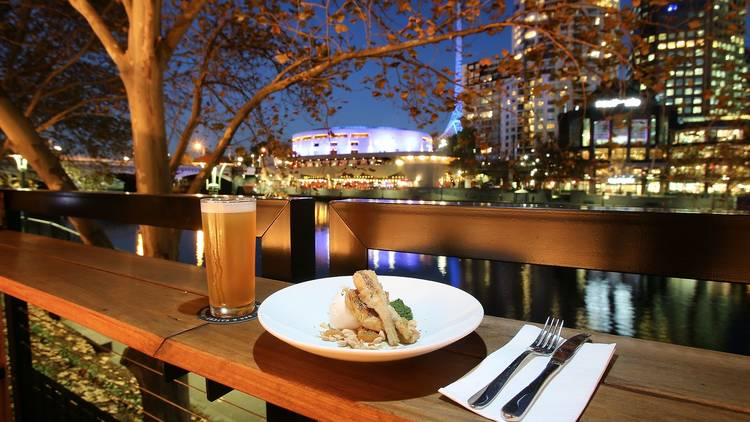 A plate of food next to a glass of beer on a bench at Arbory Bar