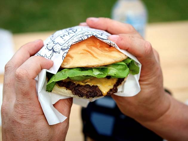 A pair of hands holding a burger