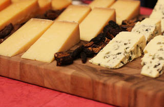 A close up shot of various cheese on a wooden board