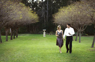 Couple strolling through the gardens with glass of wine in hand at Pokolbin