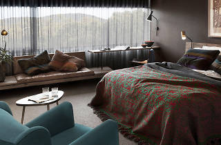 A shot of a guest room with a bed, couch and a large window overlooking trees and mountains