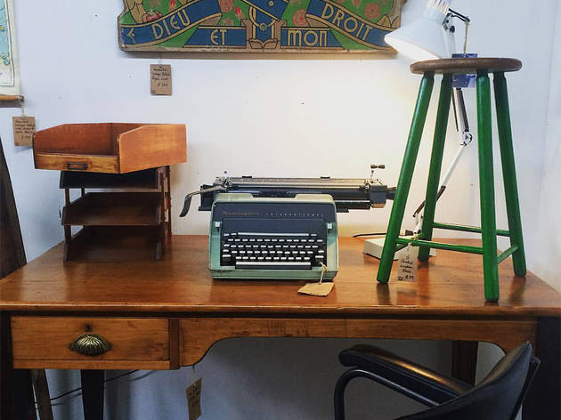 Various vintage items sit atop a vintage wooden desk at Dirty Jane's
