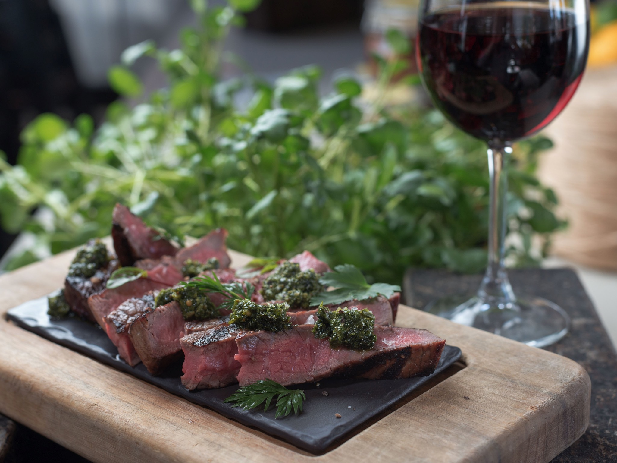 Steak served with pesto and a glass of red wine