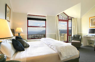 A shot of a guest room with a bed and window view of the Blue Mountains at Echoes Hotel