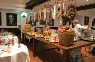 An interior shot at Machiavelli showing a centre table with various foods and hanging deli meats above it