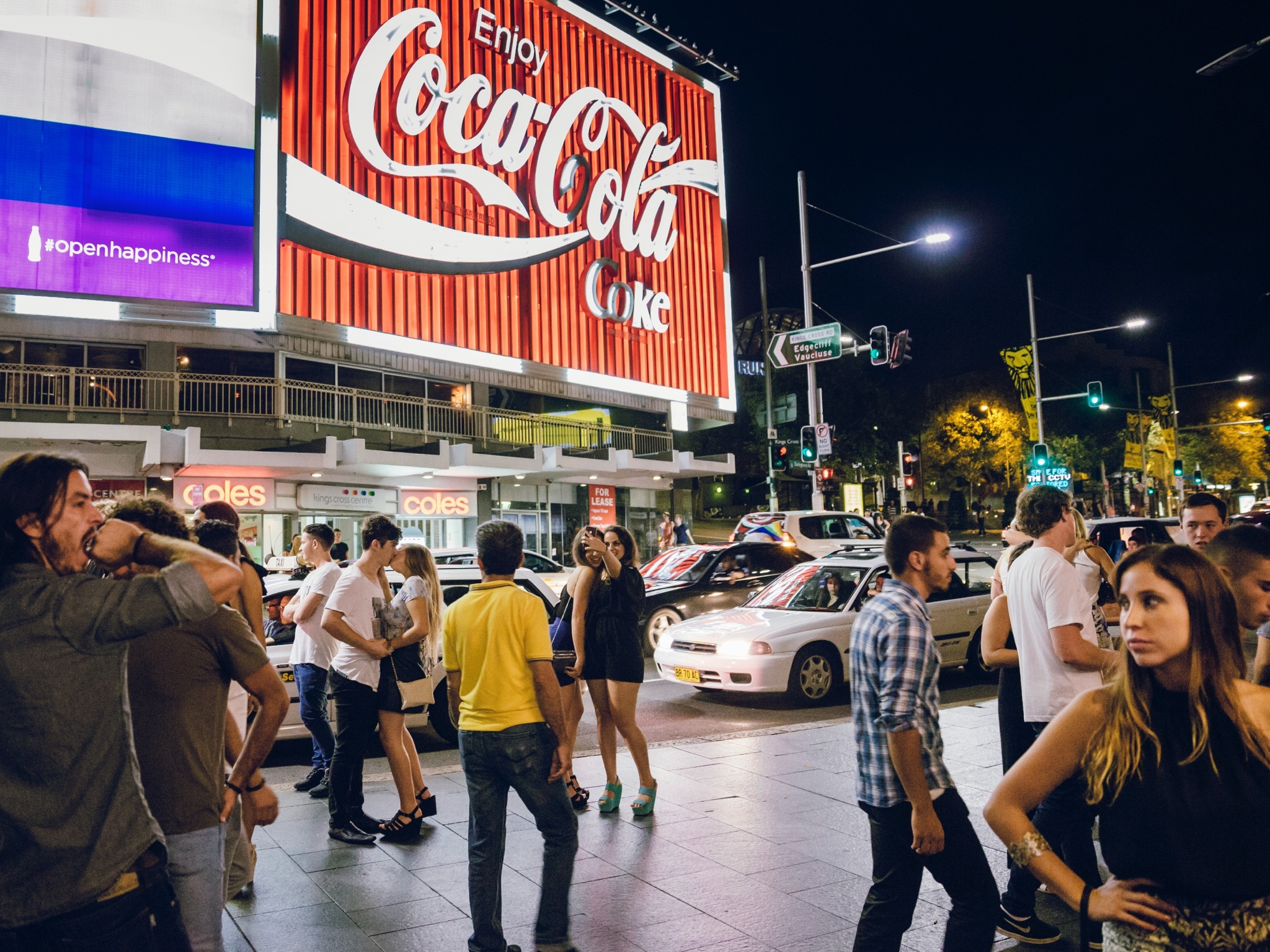 A street shot of Kings Cross in front of the Coke sign at night