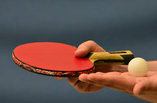 A close up shot of a table tennis paddle and ball being held in
