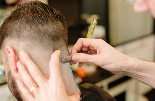 Hairdresser cuts hair with a straight razor