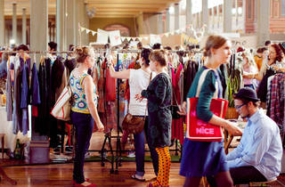 People browsing through clothing at a market stall