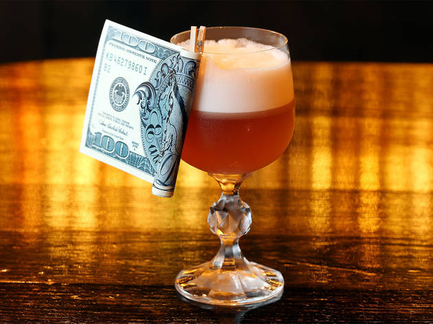 A delicious looking cocktail with a hundred dollar bill pegged to the rim