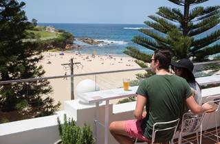 A couple sitting on the rooftop at Coogee Pavillion having a bee