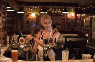 A bartender behind the bar at Frankie's Pizza by the Slice pulli