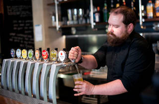 Bartender pours a beer from a tap