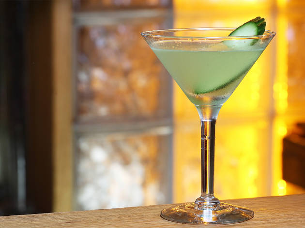 A green cocktail garnished with cucumber