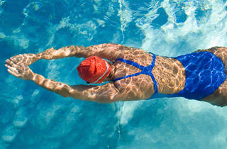 A swimmer kicks off from the pool wall