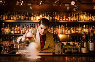 A bartender behind the bar at Eau De Vie pouring a steaming cock